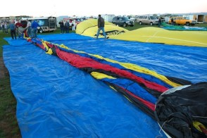 Ballooning is an early morning event. The warmer the day, the hotter the air inside the balloon must get to make the balloon rise; too hot and the nylon may weaken. So, in the cool hour before dawn the pilots and crews arrive and begin laying out the fabric gas bags, most of which are made of ripstop nylon. The bags are about 80 feet long. (The envelopes in the photo are on tarps. Last week's rain had left parts of the field muddy.)