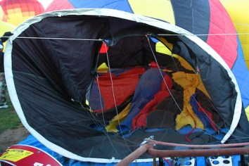 Once laid out, the envelope is cold inflated using a gasoline powered fan to blow air into the envelope. To fully inflate, a typical two-three passenger balloon requires about 100,000 cubic feet of air (2,800 cubic meters). This is done with the envelope lying on its side, and with crew members tugging and pulling in appropriate ways. In this photo you can see part of the fan (the red object with the yellow label in the lower left corner).