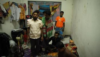 A group of migrant workers stand in a cramped and crowded room