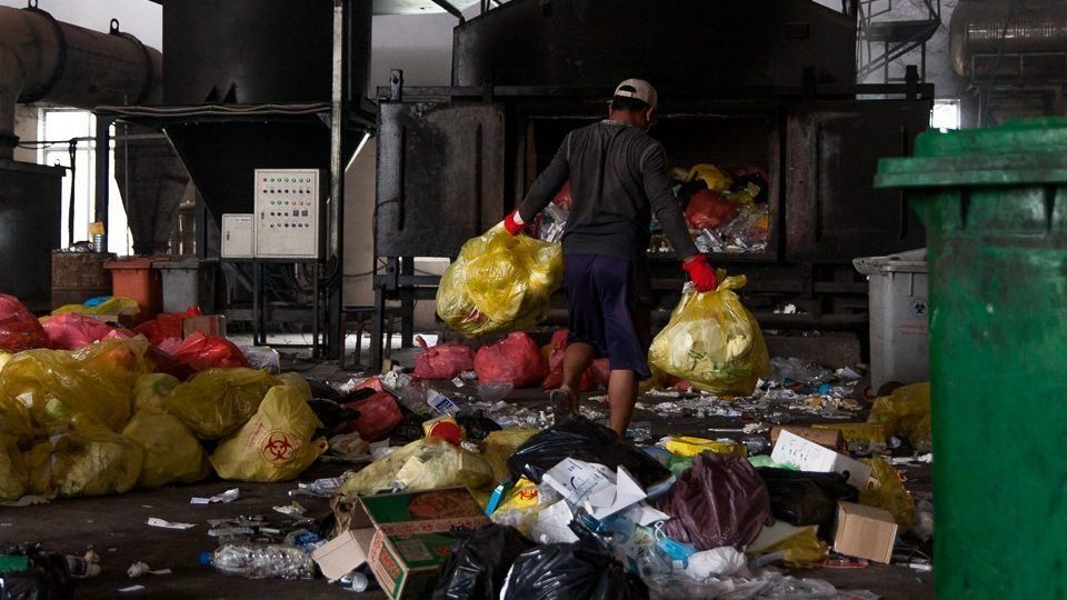 A Medical Waste Management Unit worker navigates the waste-strewn warehouse floor of the Dangkor landfill in Phnom Penh on April 9, 2020.