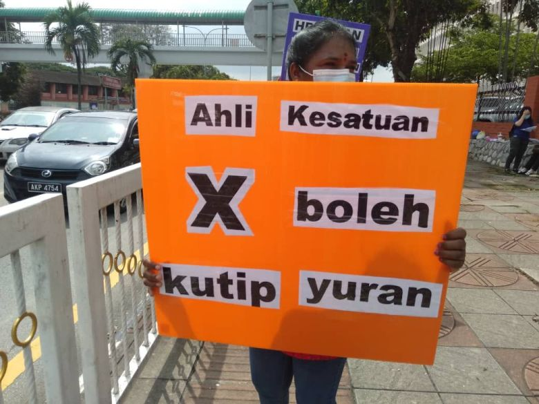 """A protestor from NUWHSAS outside Hospital Ipoh, 2 June 2020. Her sign translates to """"Union members are not allowed to collect fees"""". This refers to the union membership fees, which are required for the union to continue functioning."""