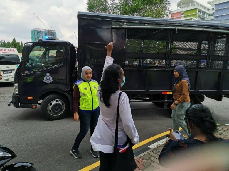 Polis menahan Saras (berbaju putih) dan penunjuk perasaan lain di luar Hospital Ipoh pada 2hb Jun 2020.