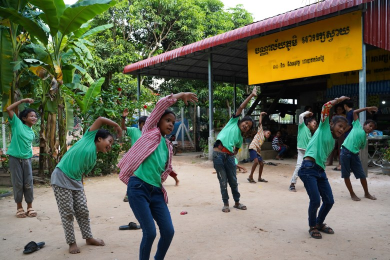 """Children come to the Village Library in Areak Svay Village to read, write, draw, exercise and socialise. Students like to wear their green shirts, which were given by a donor, when they come to the library. """"It's like their uniform,"""" Bopha says."""