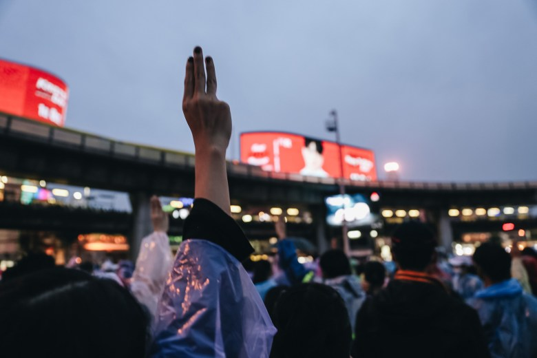 A protestor raises the movement's signature three-finger salute during a flash mob at Victory Monument in Bangkok on 18 October 2020.