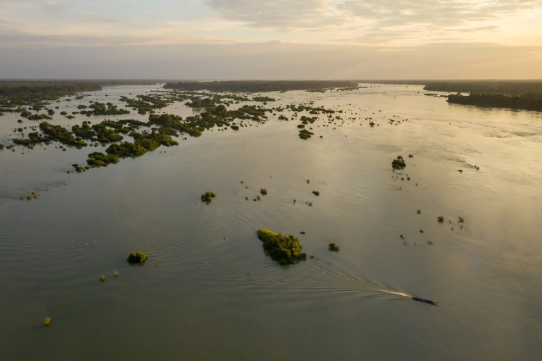 A fishing boat drives across a section of the Mekong with protected deep pools and flooded forest habitats at Kampong Kbeung Village in Kratie Province.