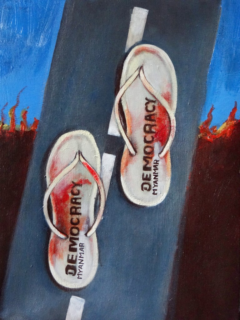 A painting of two bloodied slippers on a tar road. The text 'Democracy Myanmar' is printed on the slippers.