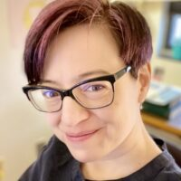 picture of a woman with short hair and glasses, smiling