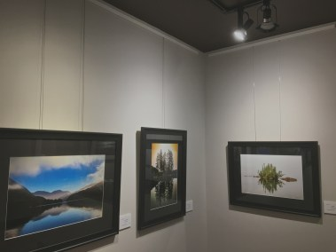 View of corner of gallery with three prints hanging.