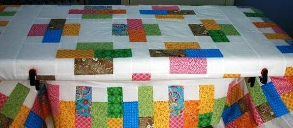 Quilt being basted on a table top