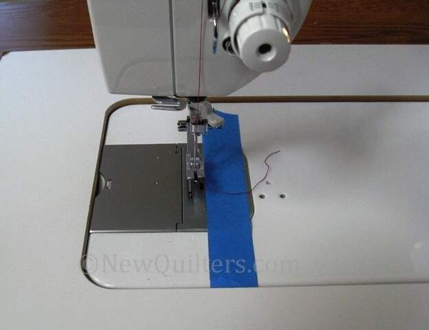 Photo of sewing machine presser foot and blue painter's tape seam guide