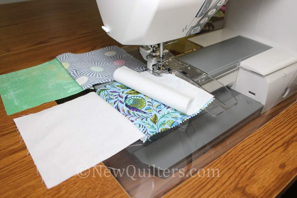 Photo showing fabric squares being sewed together