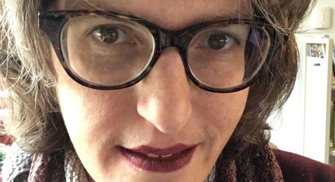 Brown haired white woman with glasses and dark lipstick