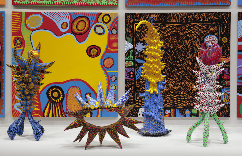 """Installation view of """"Yayoi Kusama: Infinity Mirrors"""" at the Hirshhorn Museum and Sculpture Garden, 2017. Left to right: <em>Living on the Yellow Land</em> (2015), <em>My Adolescence in Bloom</em> (2014), <em>Welcoming the Joyful Season</em> (2014), <em>Surrounded by Heartbeats </em>2014), Unfolding Buds</em> (2015), <em>Story After Death</em> (2014). Photo by Cathy Carver."""