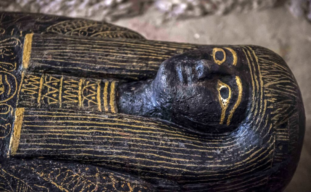 A carved black wooden sarcophagus inlaid with gilded sheets discovered by an Egyptian archaeological mission at the site of Tomb TT28, or Thaw-Irkhet-If, at Al-Assasif necropolis on the west bank of the Nile north of the southern Egyptian city of Luxor. Photo by Khaled Desouki/AFP/Getty Images.