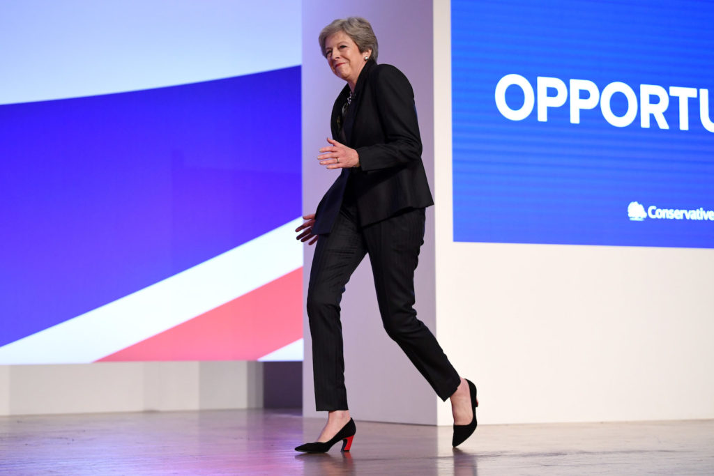 British Prime Minister Theresa May dances as she walks out onto the stage to deliver her leader's speech during the final day of the Conservative Party Conference at the International Convention Centre on October 3, 2018 in Birmingham, England. Photo by Jeff J Mitchell/Getty Images.