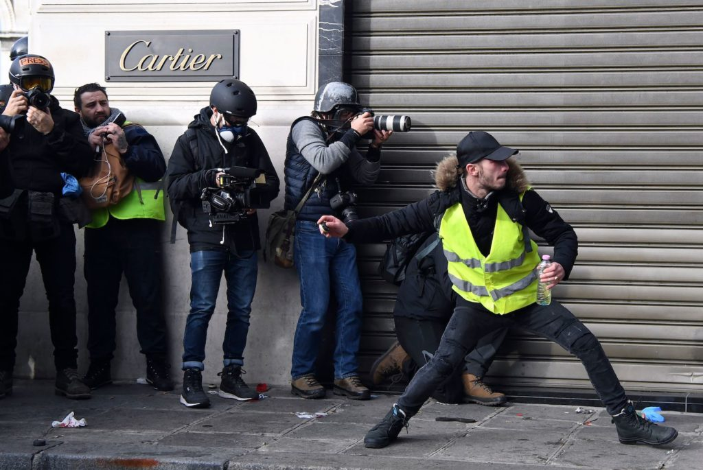 News photographers take pictures as a protestor throws a projectile near the Champs-Elysees avenue in Paris on December 8, 2018 during a