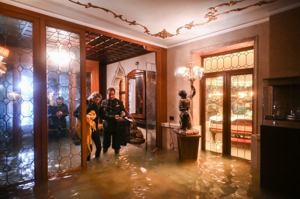 An employee of the Gritti Palace helps a customer walk across the flooded entrance during the floods on November 12 in Venice. Photo by Marco Bertorello/AFP via Getty Images.