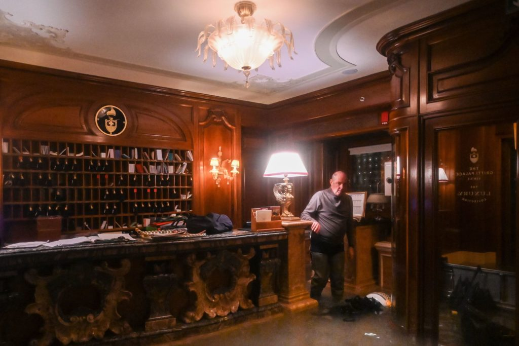 An employee stands by the flooded front desk of the Gritti Palace the floods November 12. Photo by Marco Bertorello/AFP via Getty Images.