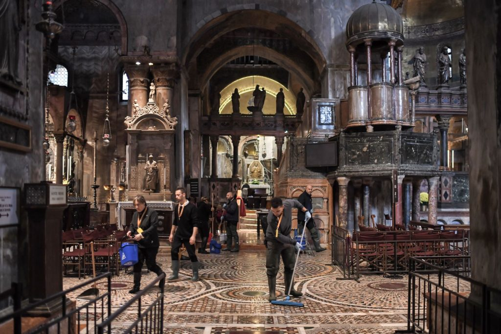 People mop the floor of the flooded St. Mark's Basilica after the floods of November 13 in Venice. Photo by Marco Bertorello/AFP via Getty Images.