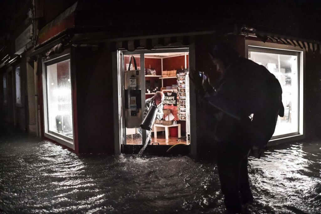 A shop owner clears his flooded premises on November 12, 2019 in Venice. Photo by Marco Bertorello/AFP via Getty Images.