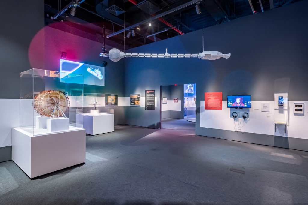 """""""Envisioning 2001: Stanley Kubrick's Space Odyssey,"""" on view at Museum of the Moving Image. A model of the Discovery One space ship hangs above a gallery. To the left is a model of the Discovery centrifuge set, designed by Harry Lange. Credit: Photo: Thanassi Karageorgiou / Museum of the Moving Image."""