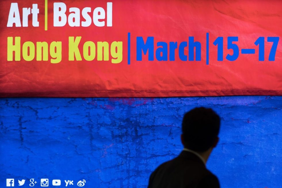 A man walks past a billboard for the Art Basel art fair in Hong Kong on March 13, 2015. Hong Kong's biggest art fair, Art Basel, opened its doors with thousands of visitors expected over the next five days. Photo by Philippe Lopez courtesy of AFP/Getty Images)