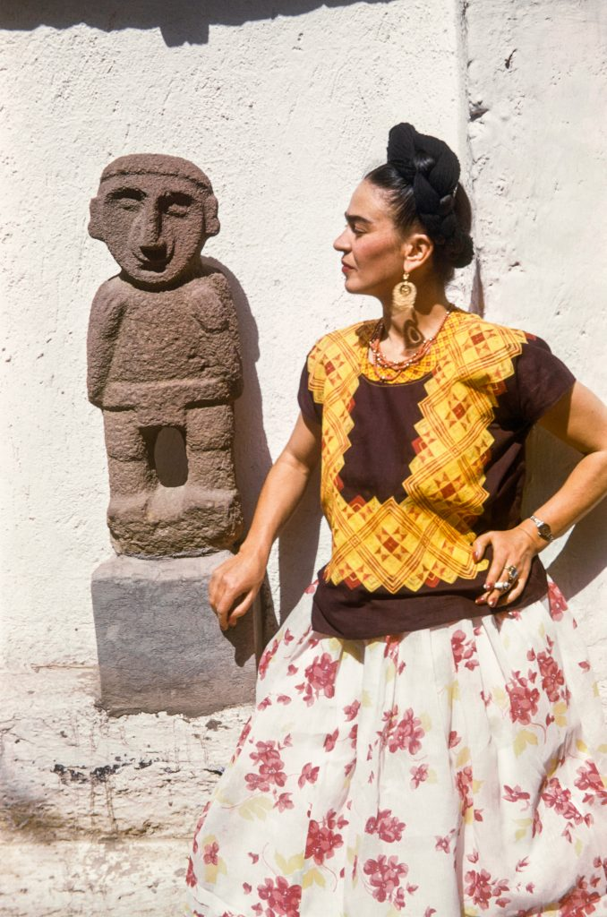 Frida Kahlo beside a Pre-Hispanic sculpture in the garden of the Casa Azul (1951). Photo ©bpk/IMEC, Fonds MCC/Gisèle Freun, ©Banco de Mexico Diego Rivera Frida Kahlo Museums Trust/VG Bild-Kunst, Bonn 2021; reproduction authorized by the Instituto Nacional de Bellas Artes y Literatura, 2021.