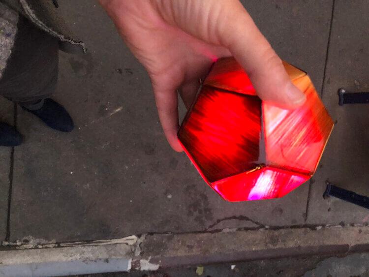 Reddish-orange light orb in a person's hand over a sidewalk