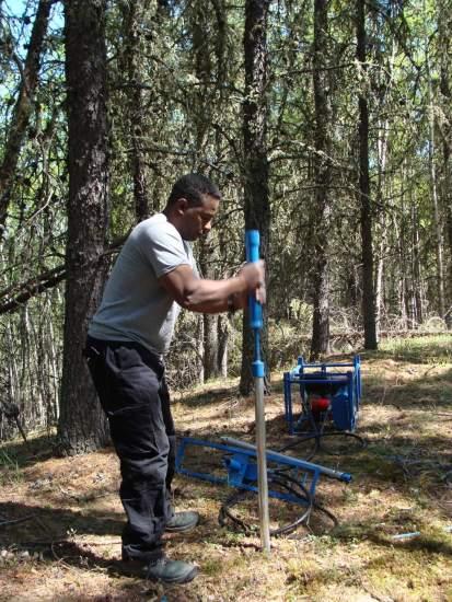 Dr. Ken Munyikwa collects geologic samples in northern Alberta.