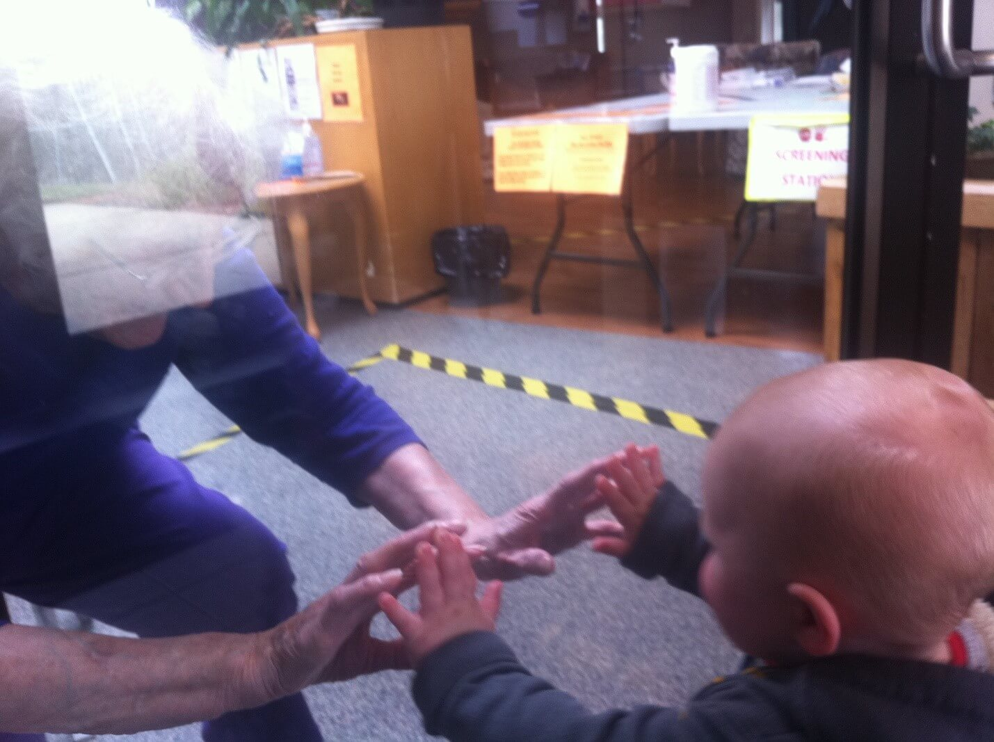 Child visiting grandparent while physically distancing