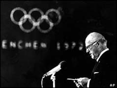 Preşedintele CIO, Avery Brundage cu logo-ul olimpic în fundal