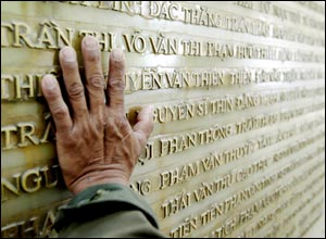 Vo Hung Son, 51, reaches to touch his fathers name on a wall of names of soldiers killed during war with the French