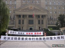 Residents hold banners outside the Chongqing court praising Wen's  execution on 7 July 2010