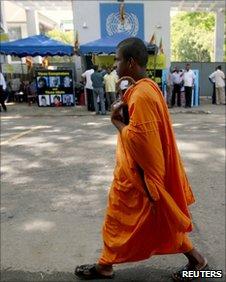 Buddhist monk walks past anti-UN protesters