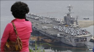 A woman looks at the USS George Washington in Busan in South Korea on 24 July, 2010