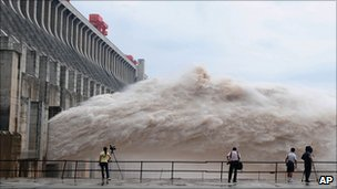 Journalists film as water is released from the Three Gorges Dam in Yichang, China (20 July 2010)