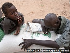 People sitting next to food aid