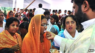Indian Catholic priest hands out the Eucharist