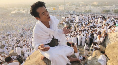 A Muslim pilgrim prays on Mount Mercy on the plains of Arafat, outside the holy city of Mecca, on Monday