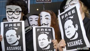 Masked demonstrators hold posters calling for release of Wikileaks founder Julian Assange (Madrid, 11 December 2010)