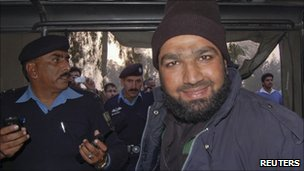 A man identified as Malik Mumtaz Hussein Qadri is driven away by police after the killing