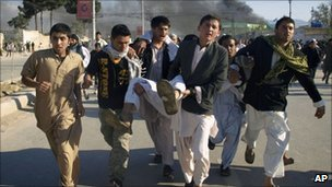 People carry an injured person in Mazar-e Sharif, Afghanistan (1 April 20110