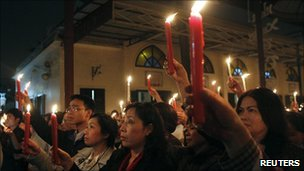 Lawyer Cu Huy Ha Vu's wife Nguyen Thi Duong Ha (C) holds a candle at a vigil for his release in Hanoi on 2 April 2011