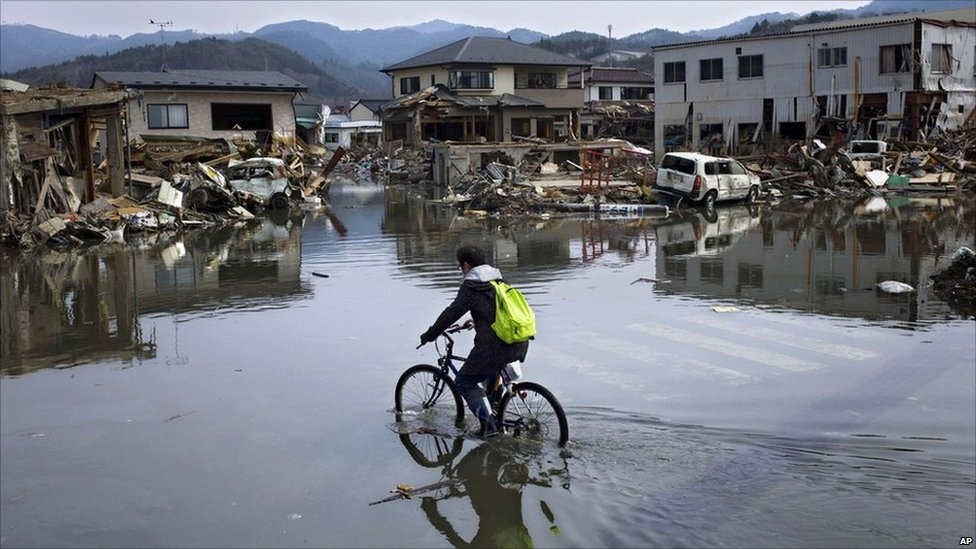 Japanese man rides a bicycle along a flooded street in the port town of Kesennuma, Miyagi, 11 April 2011