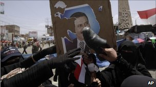Yemeni women pelt a poster of President Saleh with their shoes, Sanaa, 17 April