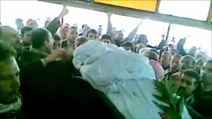 A body is brought out for burial in Syria's Deraa region, 23 April