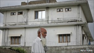 A resident walks past Osama Bin Laden's compound in Abbottabad, Pakistan