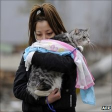Woman holding pet cat in a tsunami devastated street in Japan
