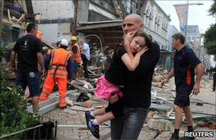 A man in Christchurch carrying a young girl through stricken streets