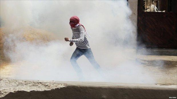 Palestinian runs through smoke during protest at Qalandiya checkpoint, near the West Bank city of Ramallah, 15 May 2011